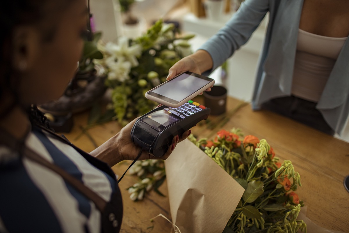 Close up of a young woman paying for a bouquet with her phone