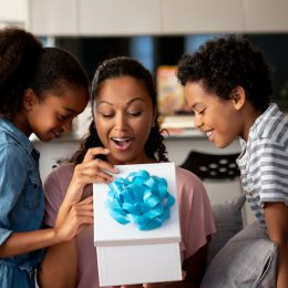 Kids surprising their mother with a gift at home and smiling