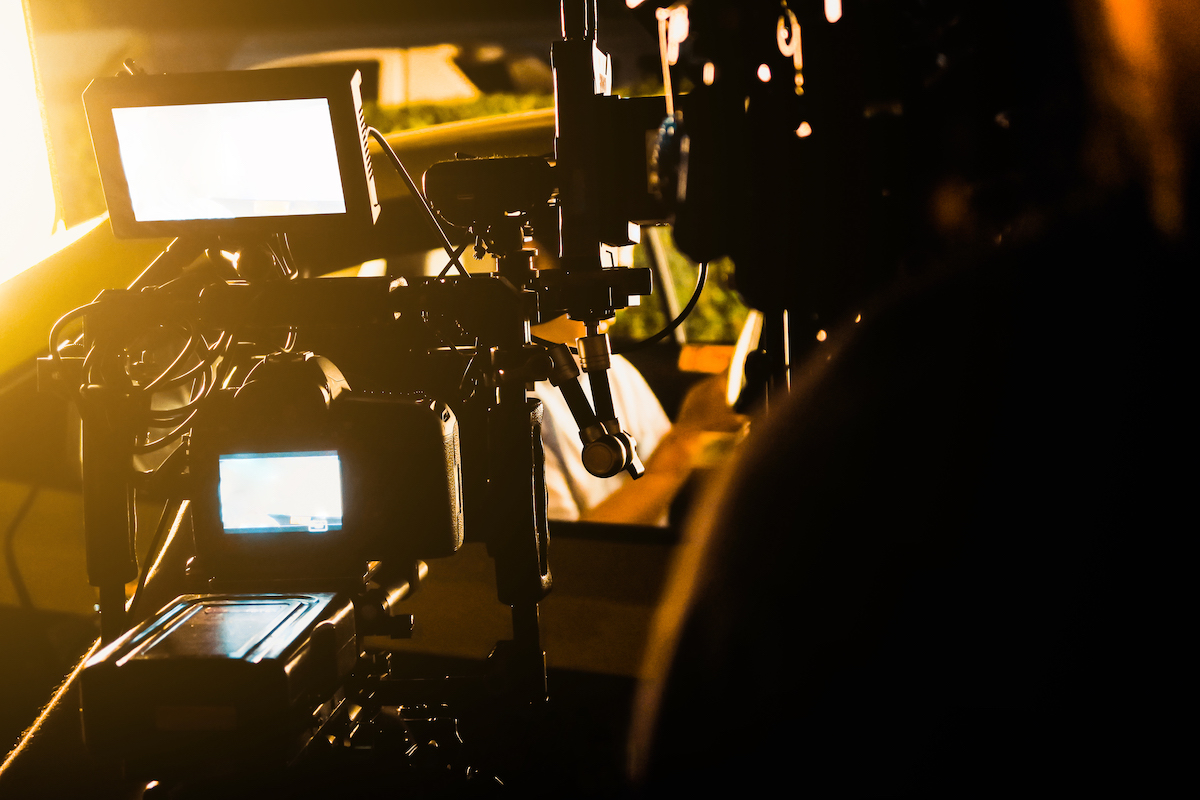 Cameraman shooting film scene with camera