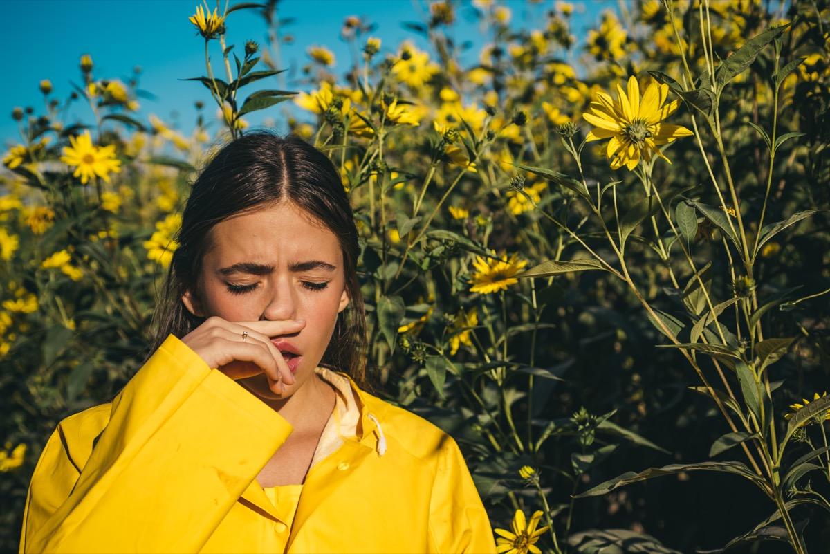 Girl sneezing near flowers