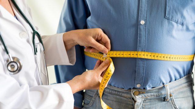 doctor measuring overweight man's waist