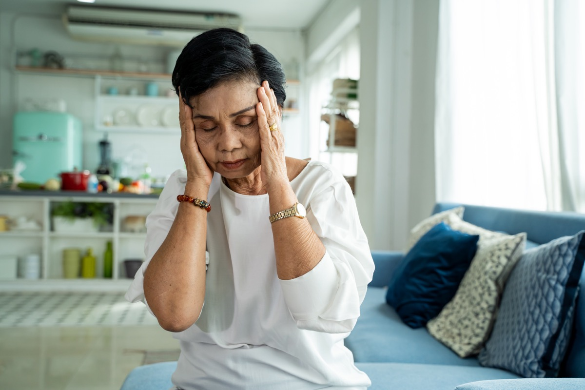 ady with closed eyes rubbing nose while sitting on sofa and suffering from headache in cozy living room at home
