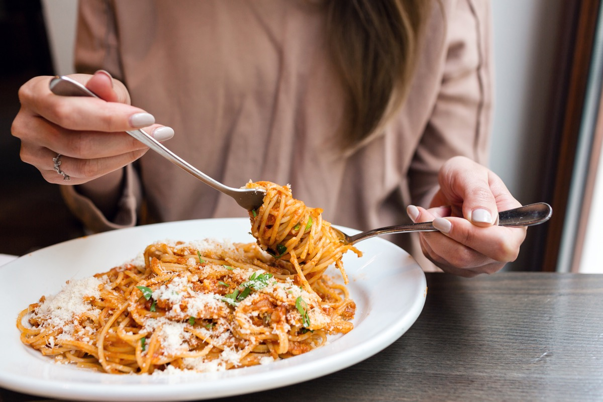 woman's hands, eating spaghetti in a bowl