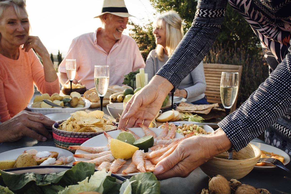 people eating outside, mediterranean food on table