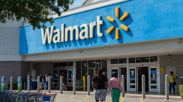 people walking into a walmart store on a sunny day