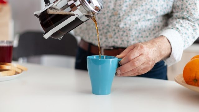 person making coffee using french press
