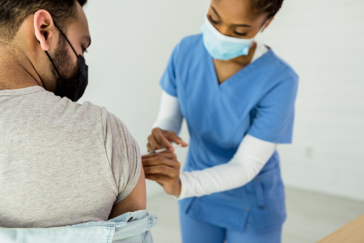 The mid adult female nurse administers the COVID-19 vaccine into the unrecognizable mid adult male patient's upper arm.