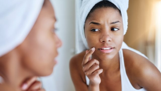shot of a young woman inspecting her skin in front of the bathroom mirror and looking upset