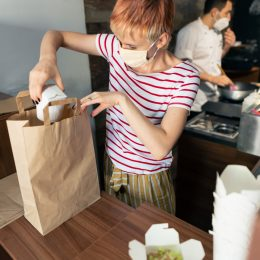 A restaurant worker packing a to-go order into a paper bag