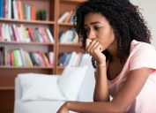 woman sitting on couch, looking sad or nervous