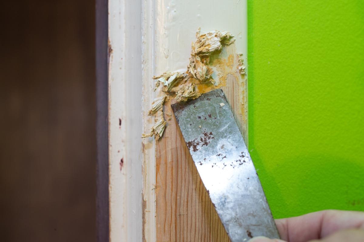 scraping paint from doorway