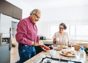 A senior couple preparing food in the kitchen