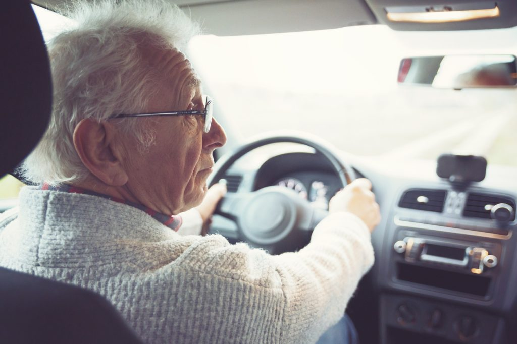 A senior man wearing glasses sitting behind the wheel of a car