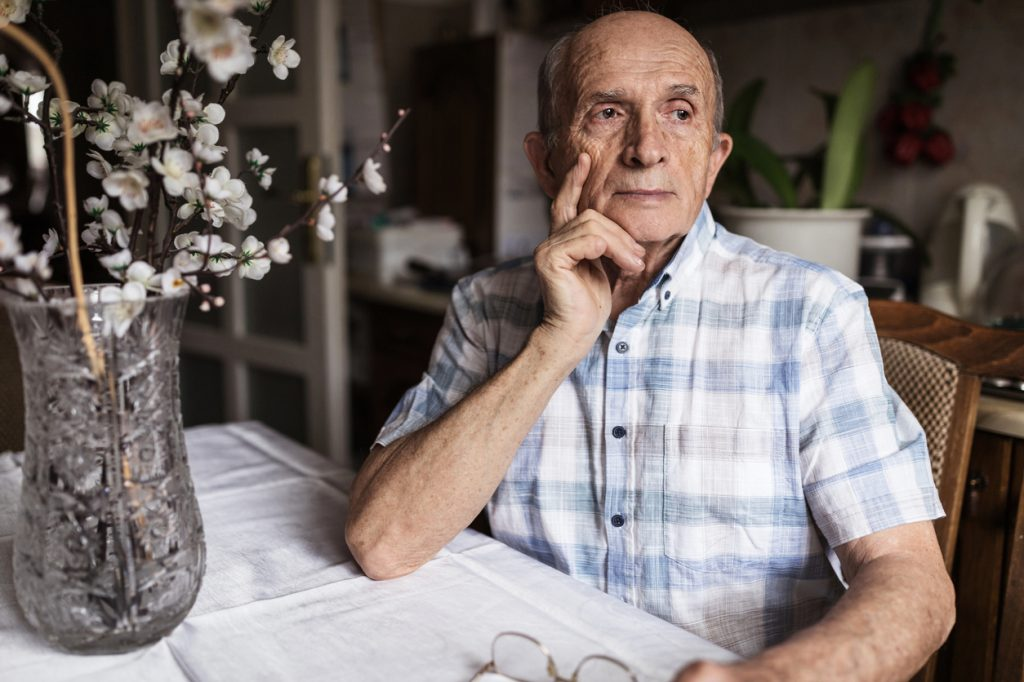 A senior man sitting at a table with a worried look on his face.