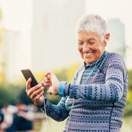 A senior woman checking her smartphone and smartwatch while exercising in a park