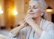 A senior woman sitting with her eyes closed while listening to headphones