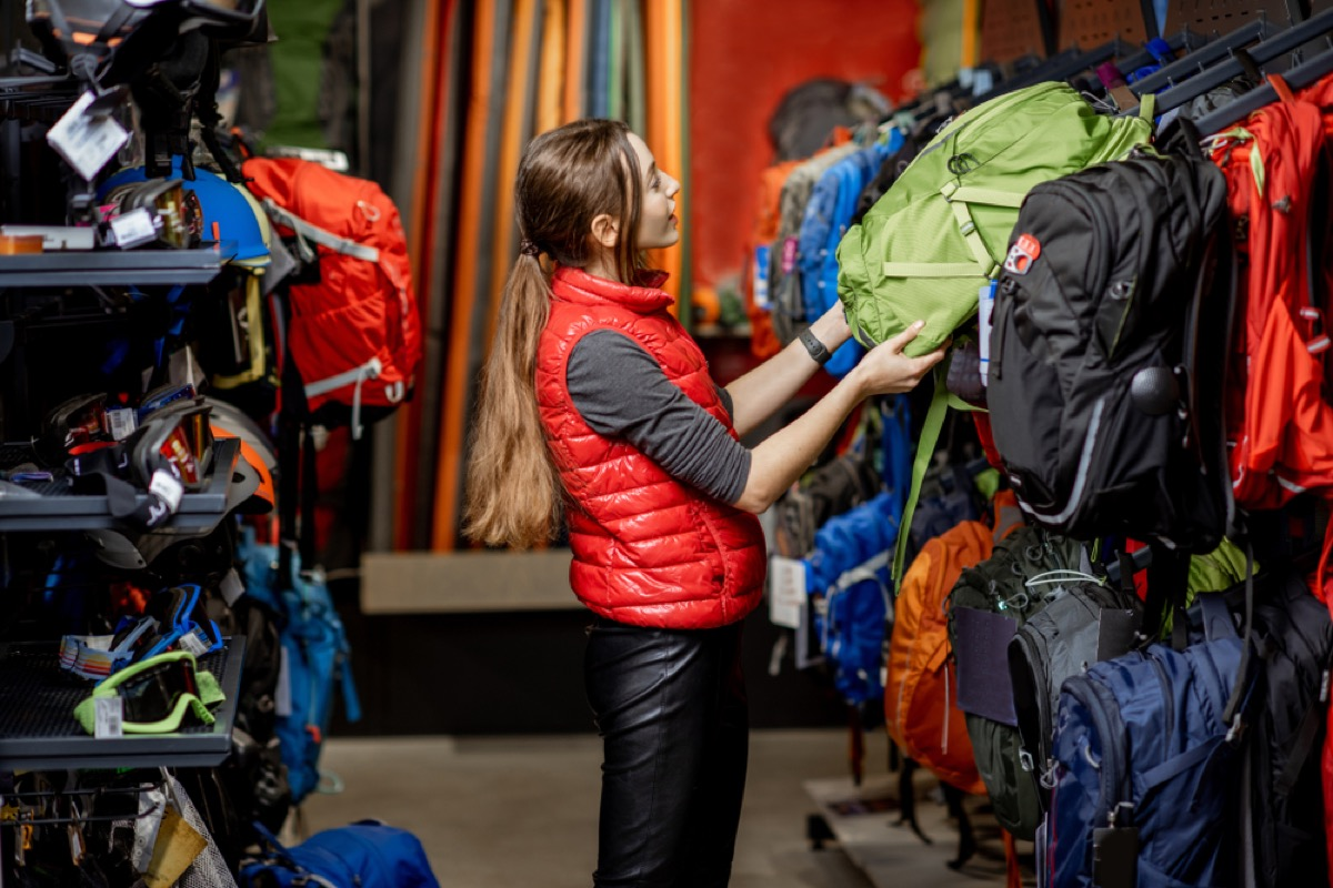 woman looking at a backpack on display at a sporting goods store