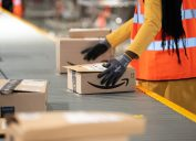 close up of amazon worker handling box at factory