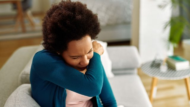 woman coughing into her arm while sitting on the couch