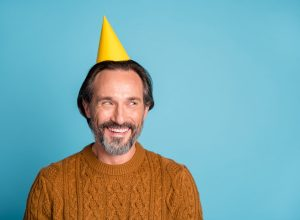 Middle aged man smiling with birthday hat on