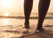 close up of legs walking into the ocean