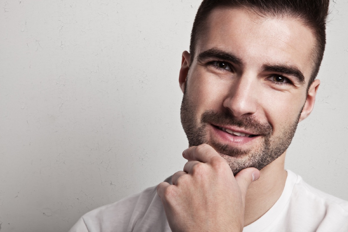 man with heavy stubble smiling with hand on chin