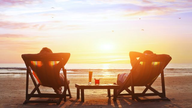 Retired couple watching sunset on the beach