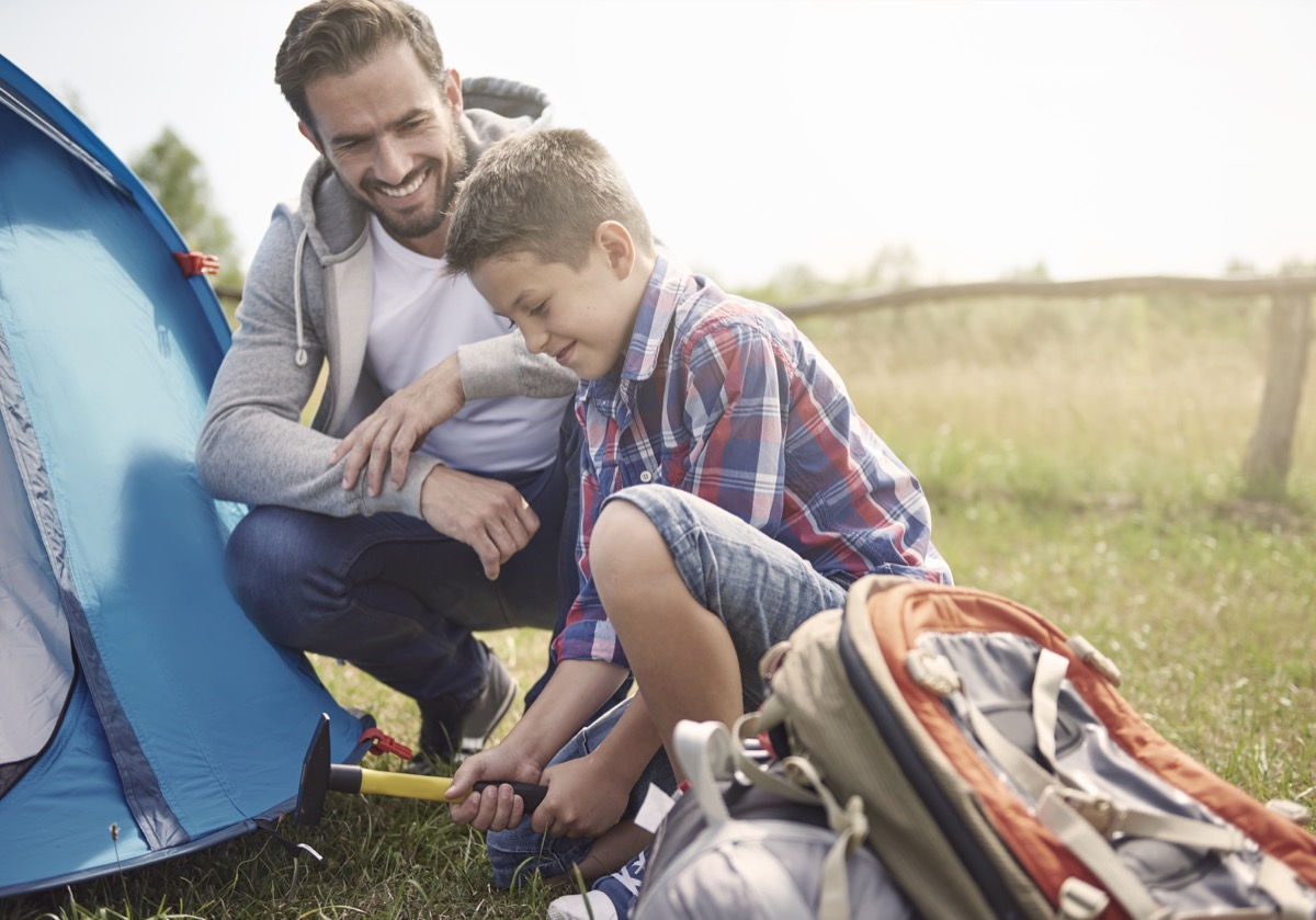 father watching son hammer nail to put up a tent outside