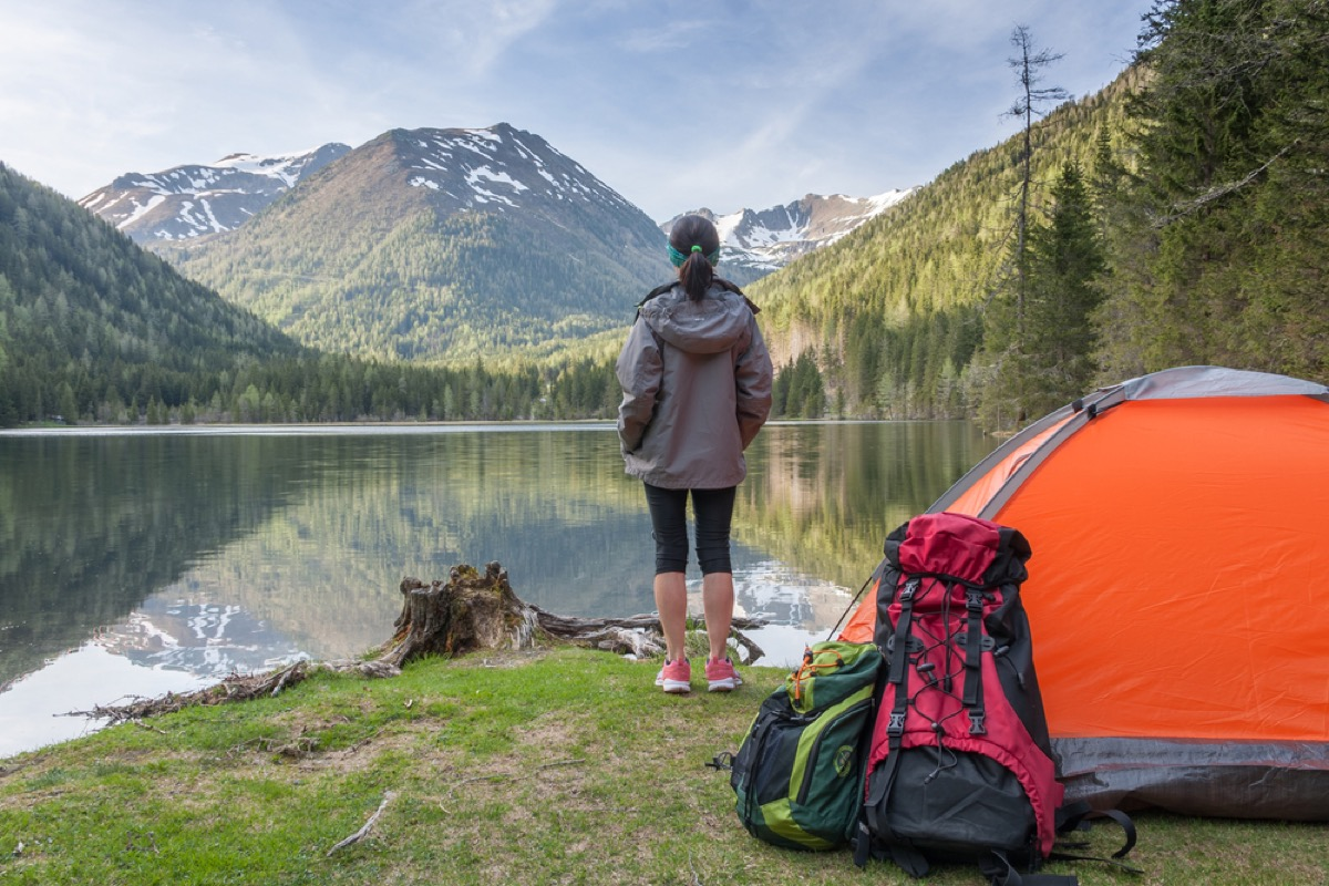 woman at lake with tent and backpack in foreground