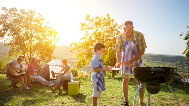 family barbecuing outside with tent in the background