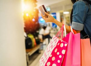 close up of woman holding credit card and carrying shopping bags