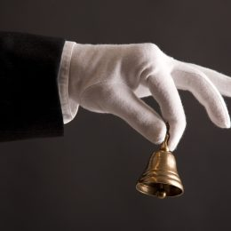 butler's hand in white glove holding a small bell