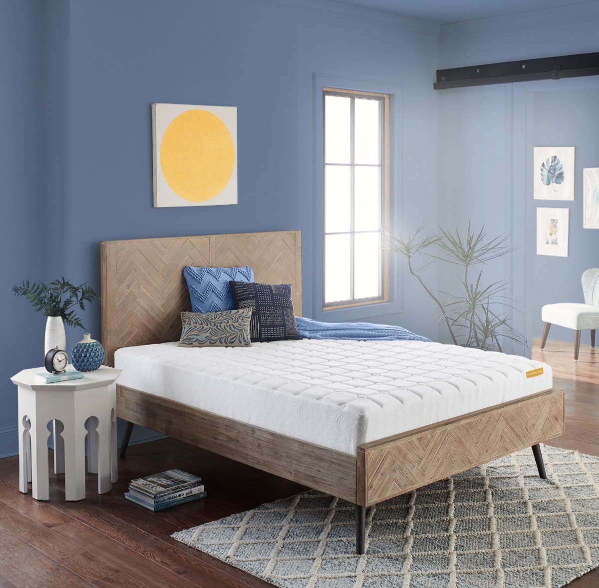 blue bedroom with undressed mattress