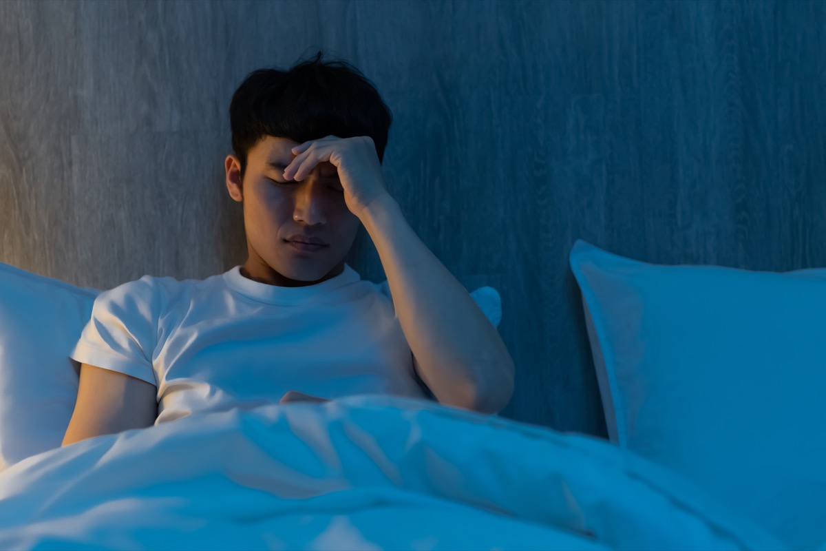 man is worrying about something on bed at night