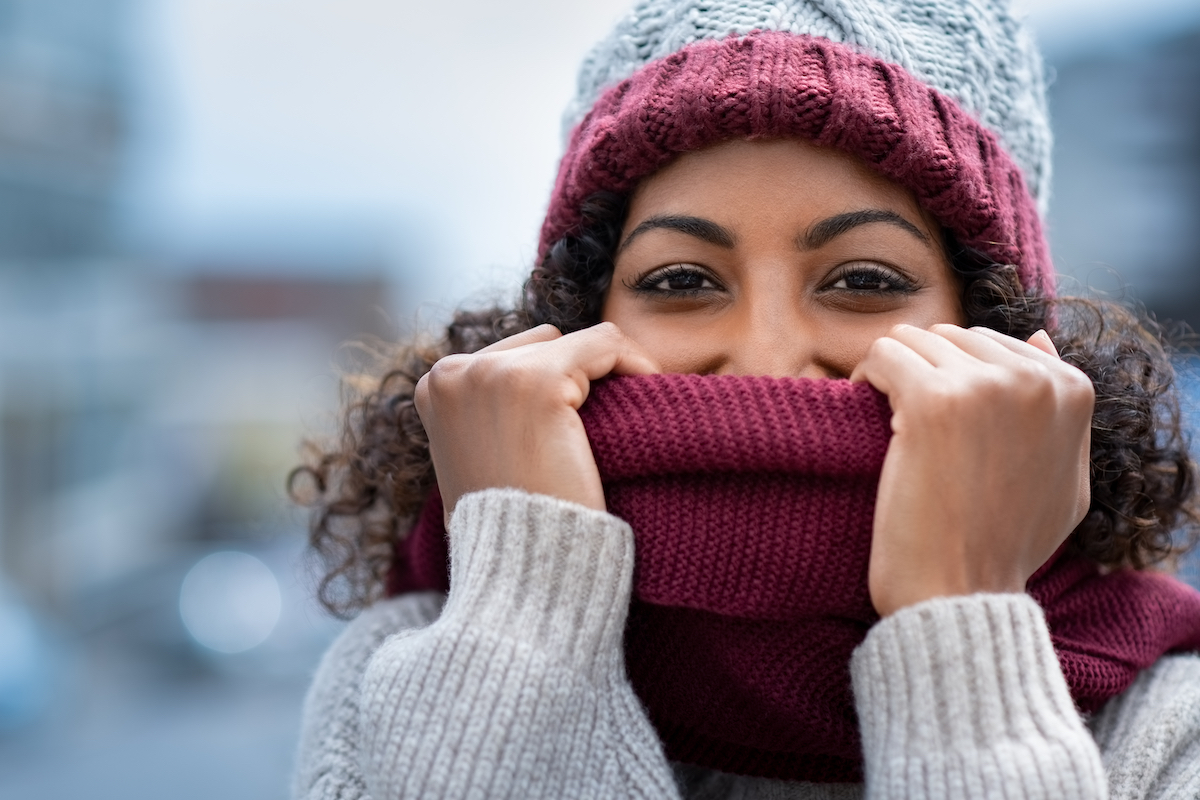 Closeup of woman holding woolen scarf with hands over nose