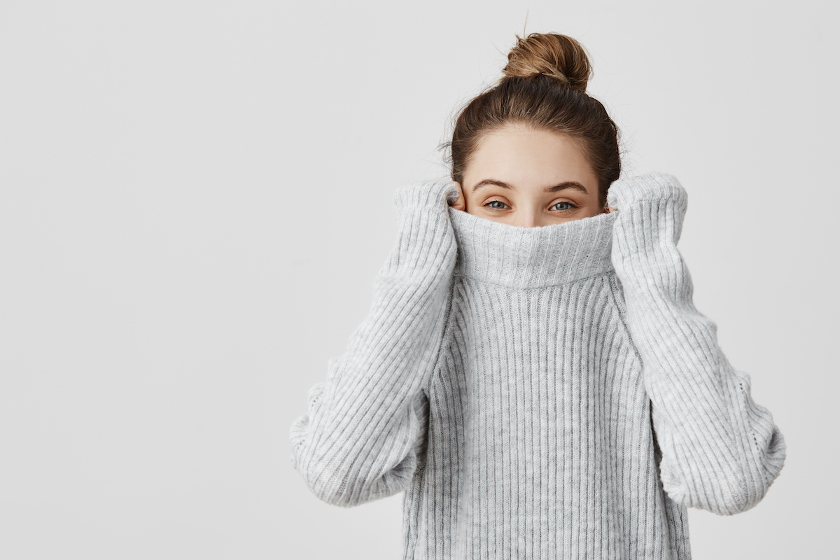 Portrait of young woman pulling her sweater over head and smelling it