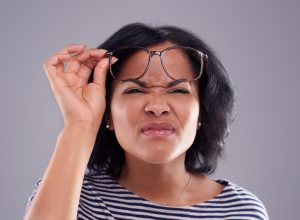 Woman struggling to see without her glasses against a grey background
