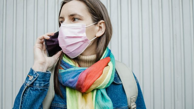 Photo of a young woman wearing a protective face mask during a pandemic, she is holding a mobile phone