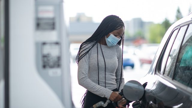 A young woman pumps gas at gas pump. She is wearing a blue medical mask and blue protective gloves.