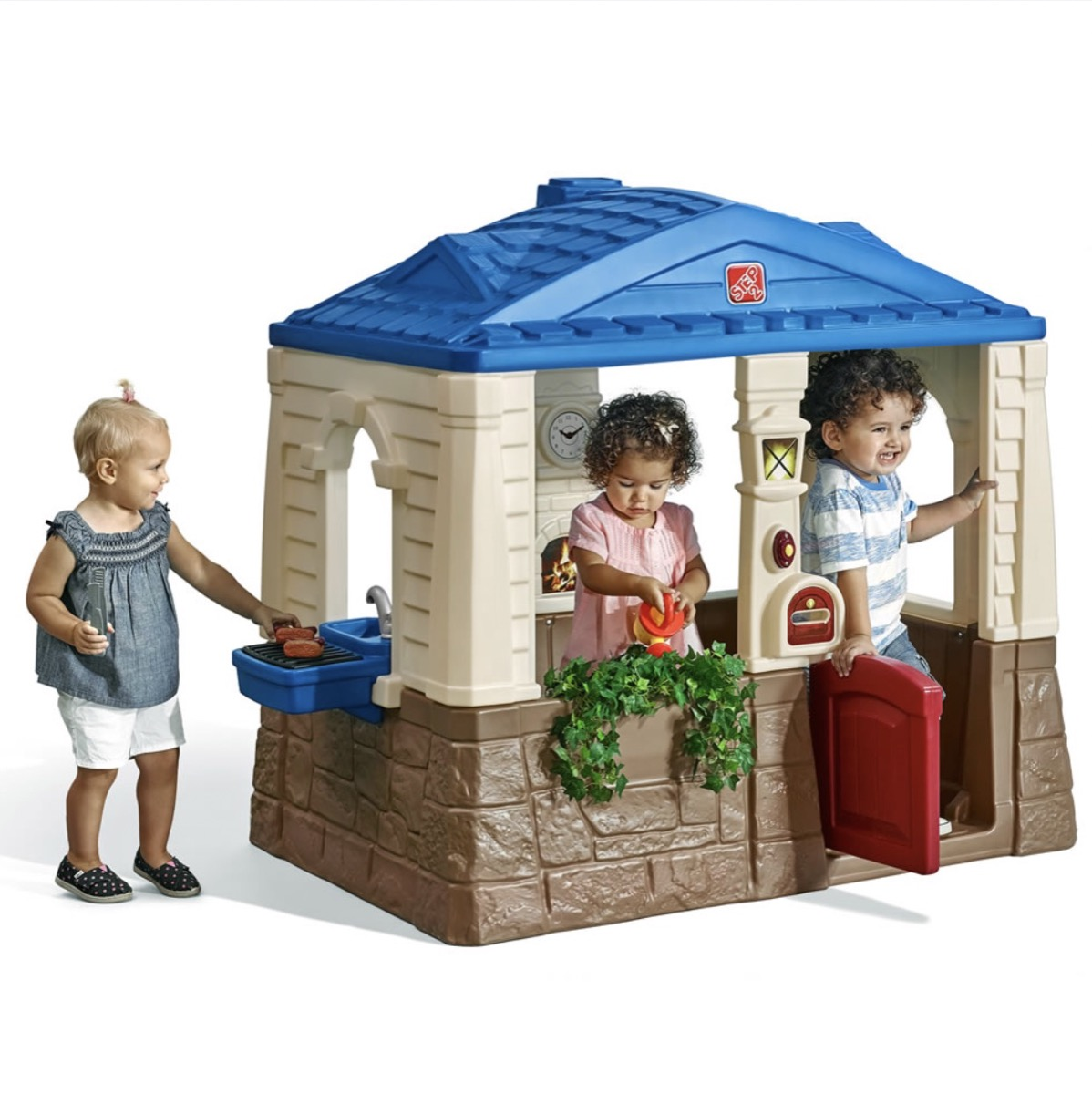 three children playing in a plastic outdoor playhouse