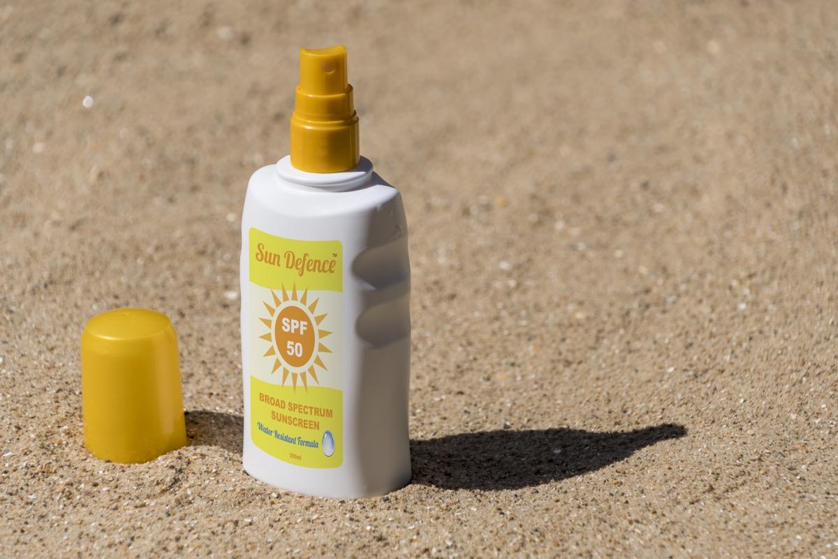 Bottle of sunscreen on the beach.