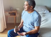 Shot of a cheerful mature man seated on his bed and about to drink medication with water in the bedroom at home during the day