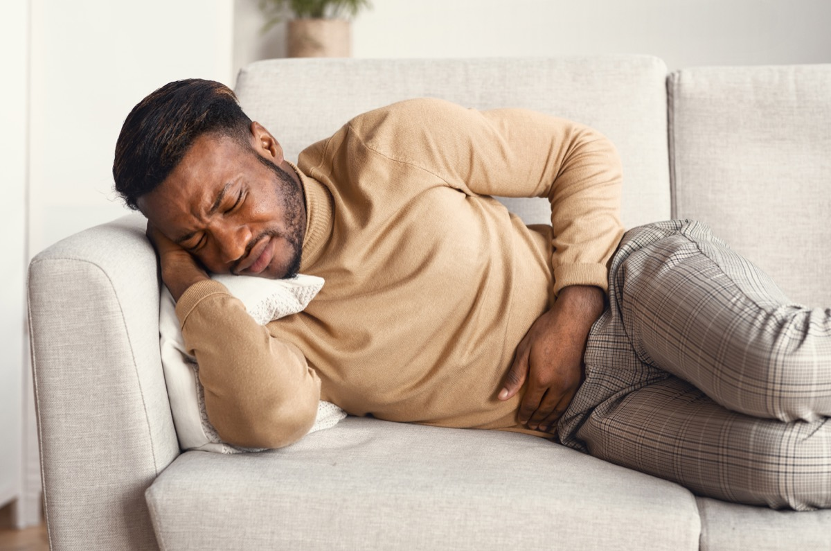 man sitting on a couch in pain, abdominal pain, hand on stomach, looking uncomfortable