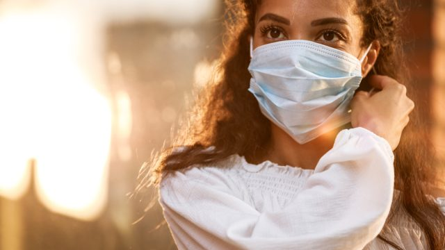 young woman taking her protective face mask off