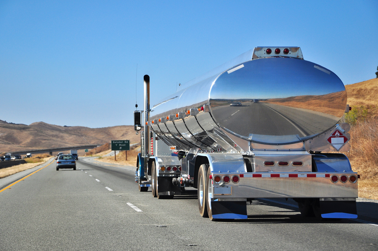 A chrome gas tanker truck driving down a highway