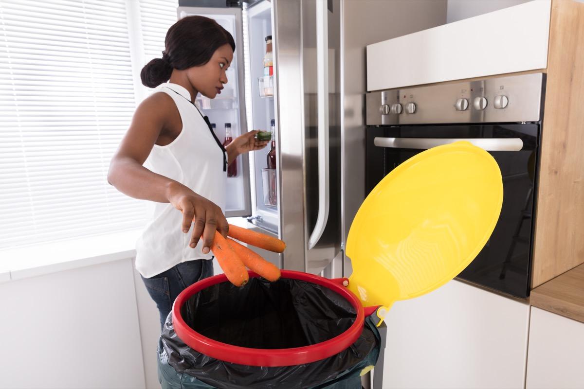 Woman Throwing Carrot In Trash Bin