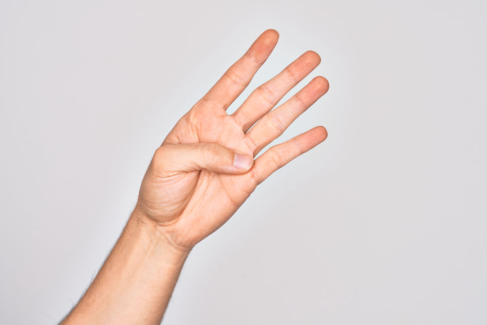 A close up of a hand with a the thumb stretched across the palm