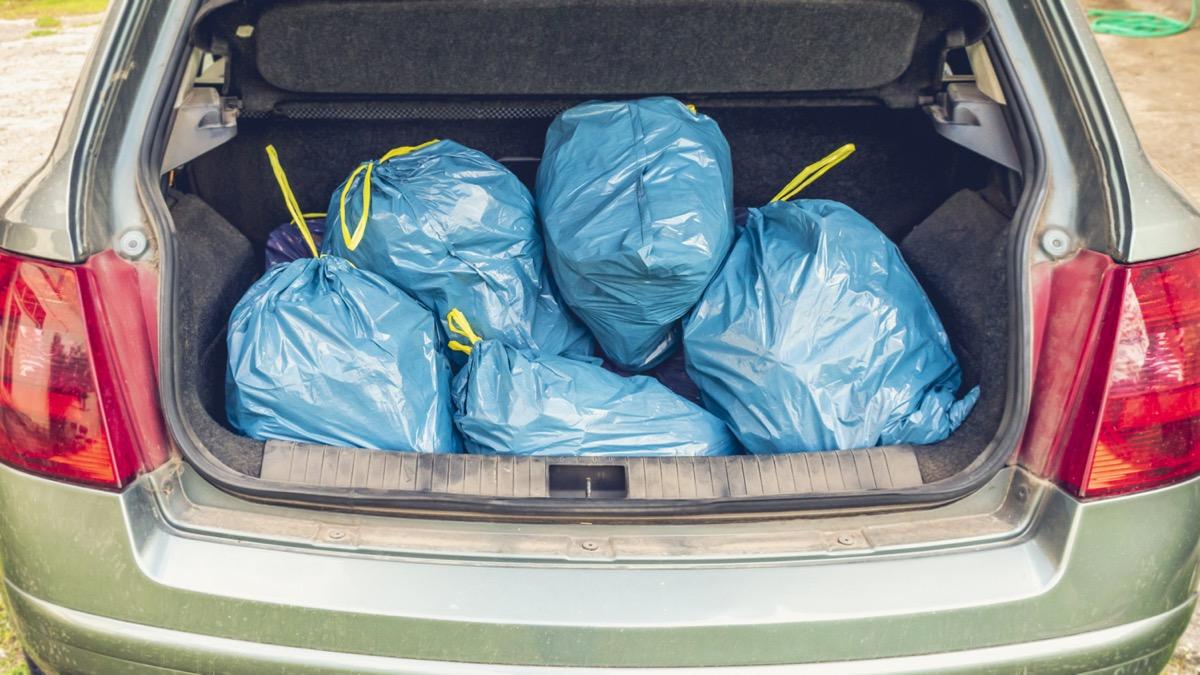 trunk full of blue plastic garbage bags