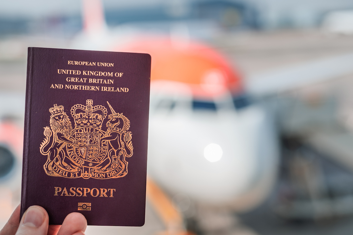 A biometric British passport being held up against a bright white and orange plane in the background