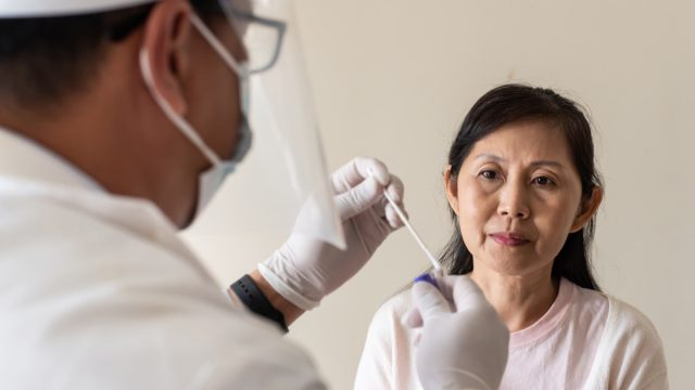 male doctor performing Covid-19 throat and swab test to a woman
